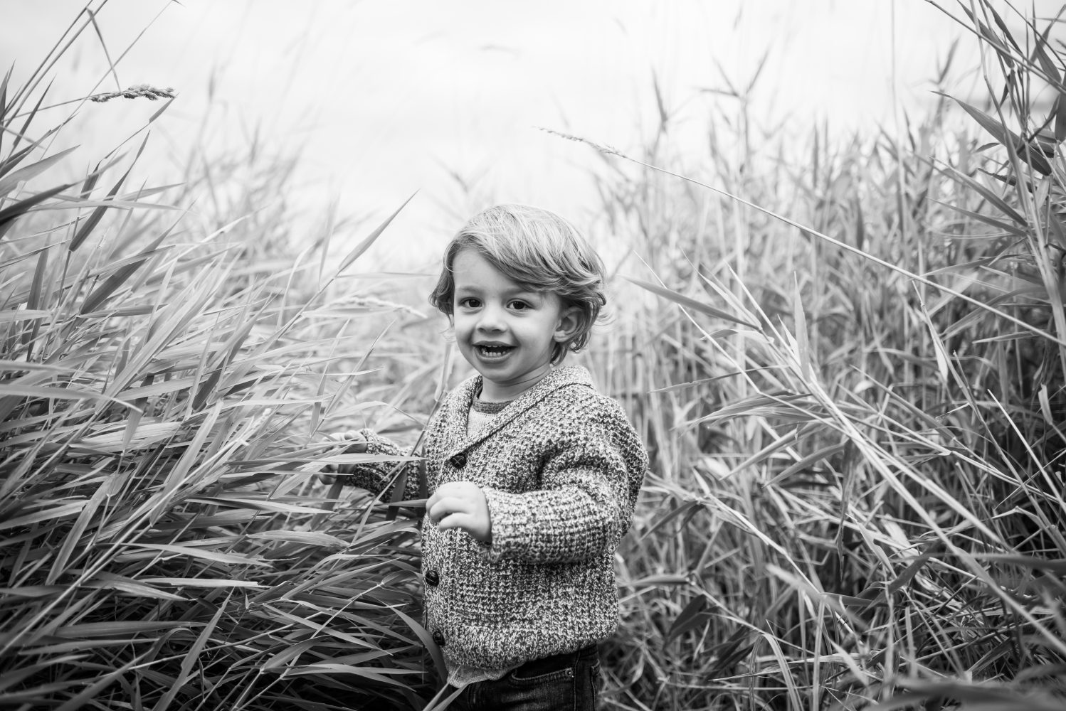 A sweet black and white photo of a young boy in the river valley | 3Haus Photographics