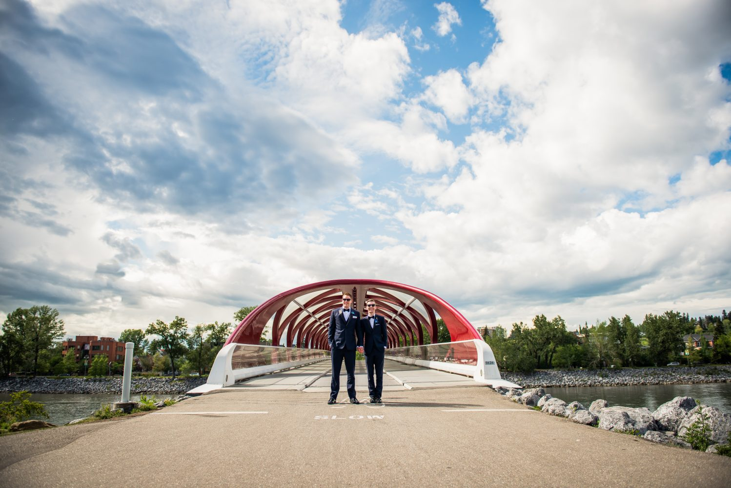 Photo of the two Grooms at Calgary's Iconic peace bridge inbetween the ceremony and reception at the Calgary Zoo | 3Haus Photographics
