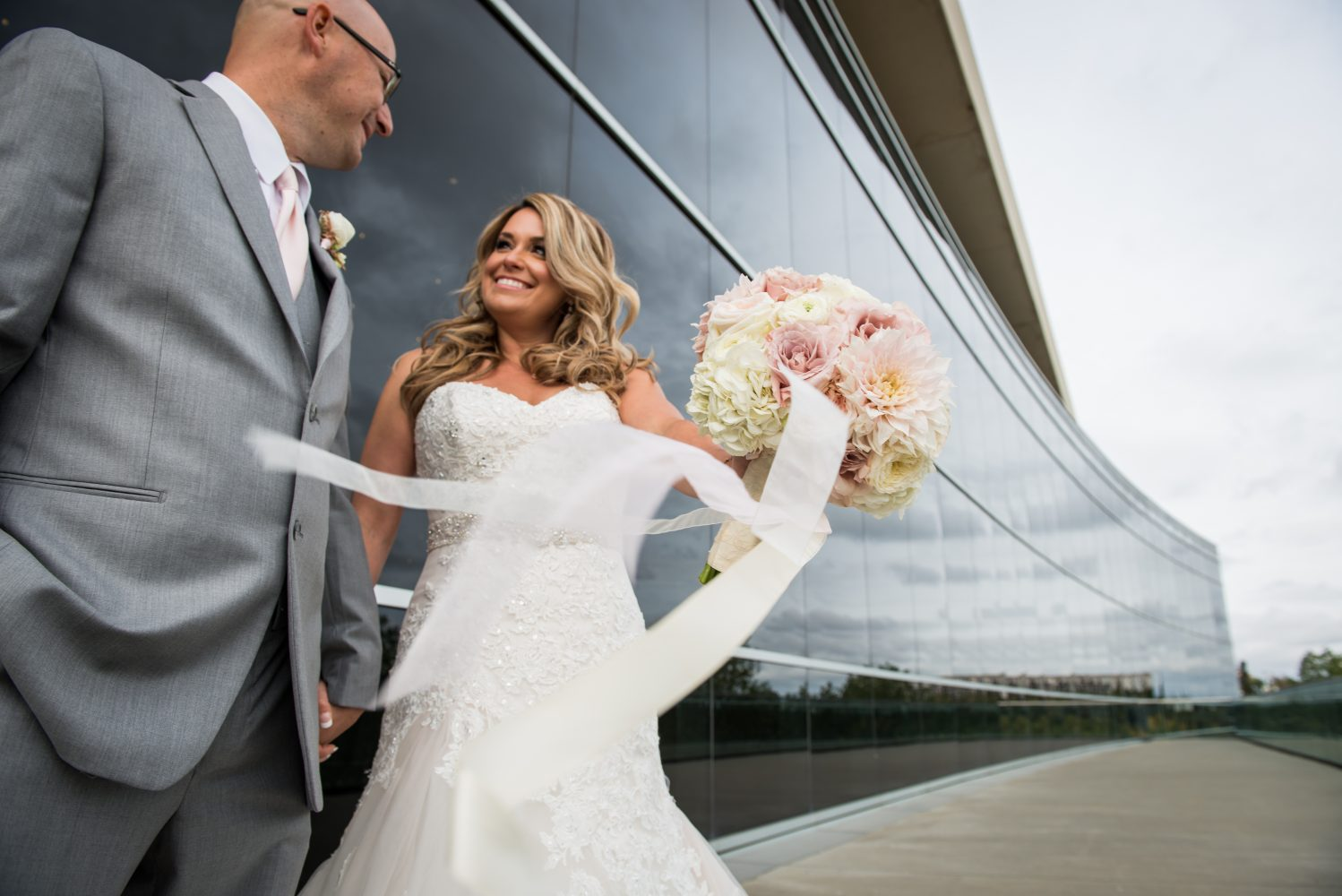A windy photograph of a stunning bride and groom with their beautiful boquet from Fabloomosity in between their ceremony and reception at the Union Bank Inn. Photo taken at the Shaw Conference Centre | 3Haus Photographics