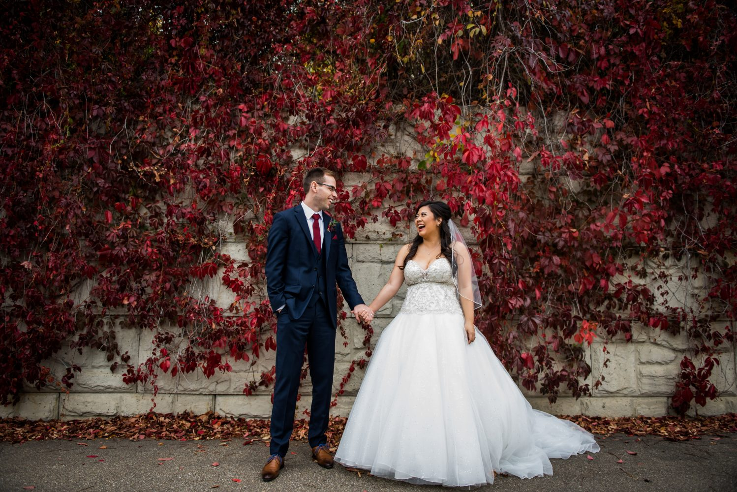 A vibrant fall wedding at the Old Timers Cabin with a beautiful vine wall at Louis Mckinney Park | 3Haus Photographics