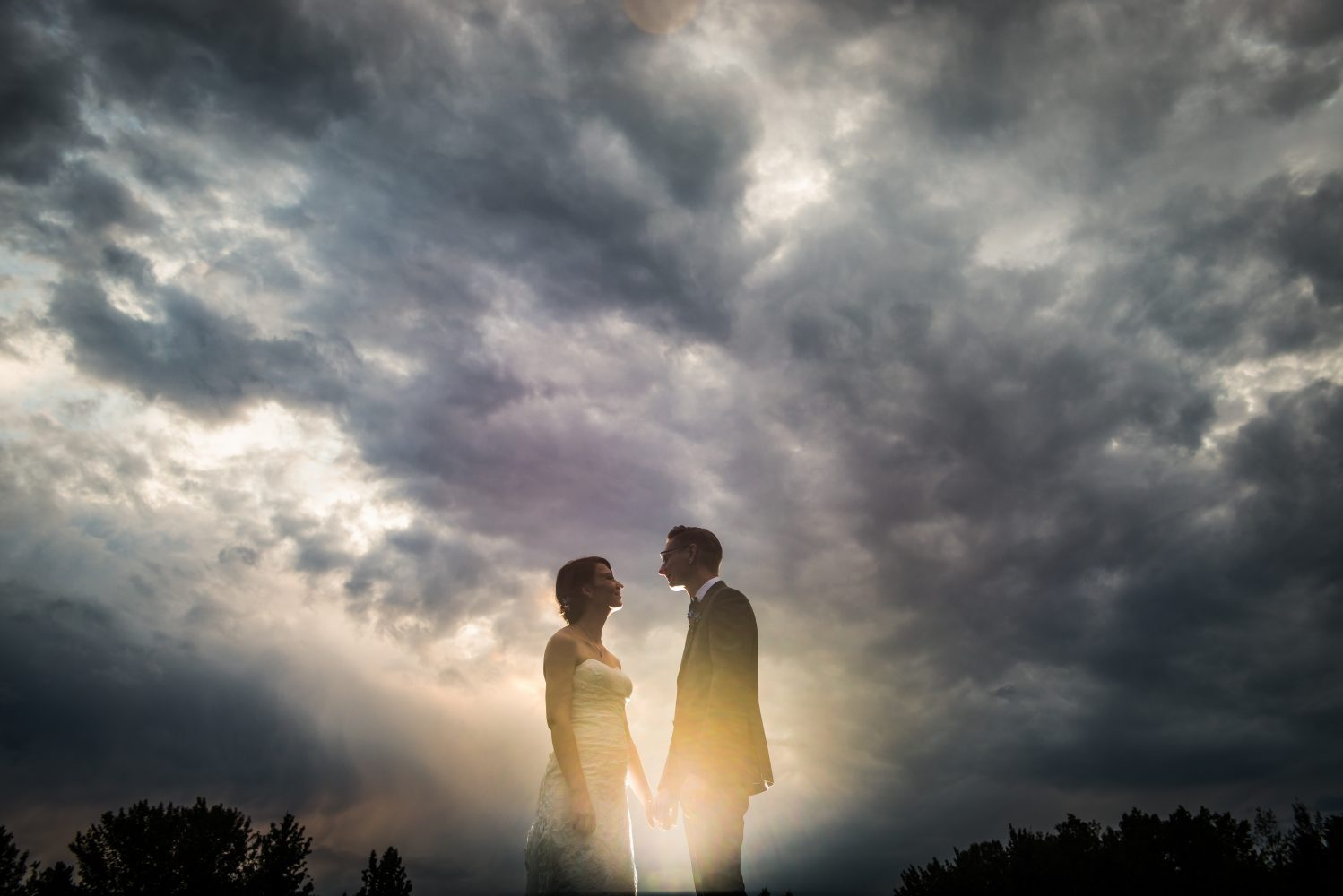 A cloudy photo of the bride and groom as a storm threatened to come. Flash photography. Rundles Mission in Pigeon Lake Alberta | 3Haus Photographics